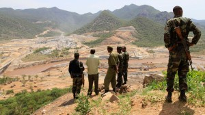 Security guards look at the construction of Ethiopia's Great Renaissance Dam in Guba Woreda, some 40 km (25 miles) from Ethiopia's border with Sudan, June 28, 2013. Egypt fears the $4.7 billion dam, that the Horn of Africa nation is building on the Nile, will reduce a water supply vital for its 84 million people, who mostly live in the Nile valley and delta. Picture taken June 28, 2013. REUTERS/Tiksa Negeri (ETHIOPIA - Tags: POLITICS SOCIETY ENERGY ENVIRONMENT) - RTX115K6